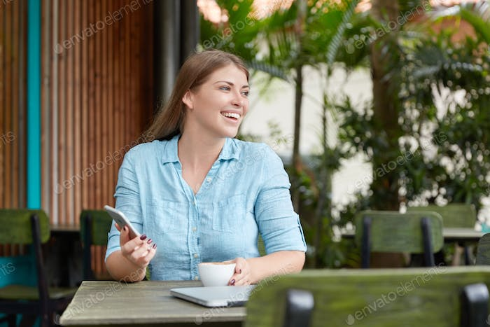Pleased satisfied young beautiful female dressed casually, holds smart phone and mug of coffee, mess