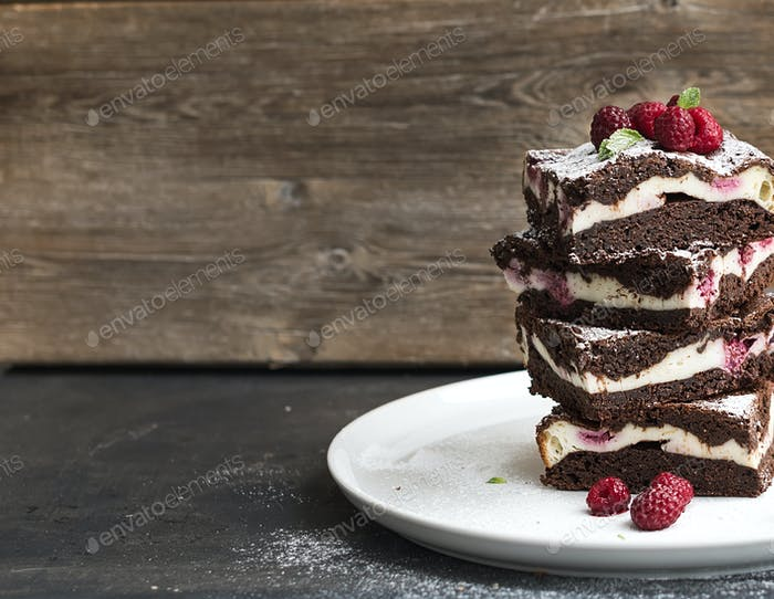 Thumbnail for Brownies-cheesecake tower with raspberries on white plate, wooden backdrop, copy space