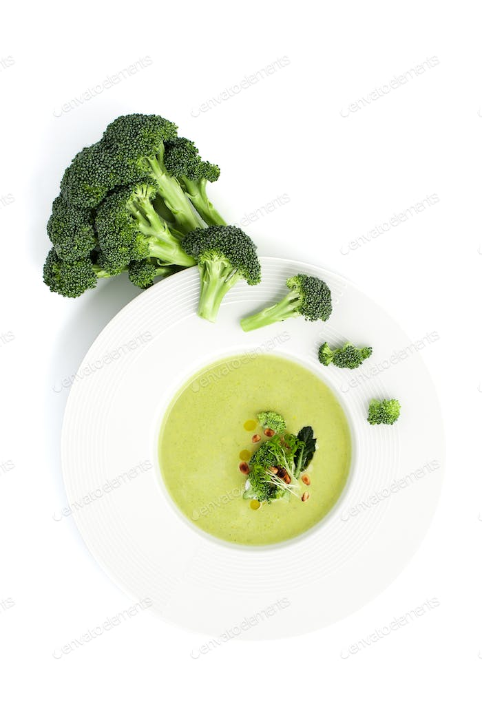 Cream of broccoli soup in a white plate on a light background.