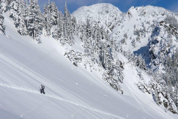 54837,Snowshoer walking up snowy hillside
