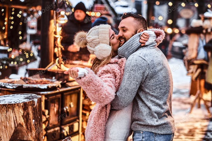 Attractive couple wearing warm clothes near a shop of a winter fair at a Christmas time