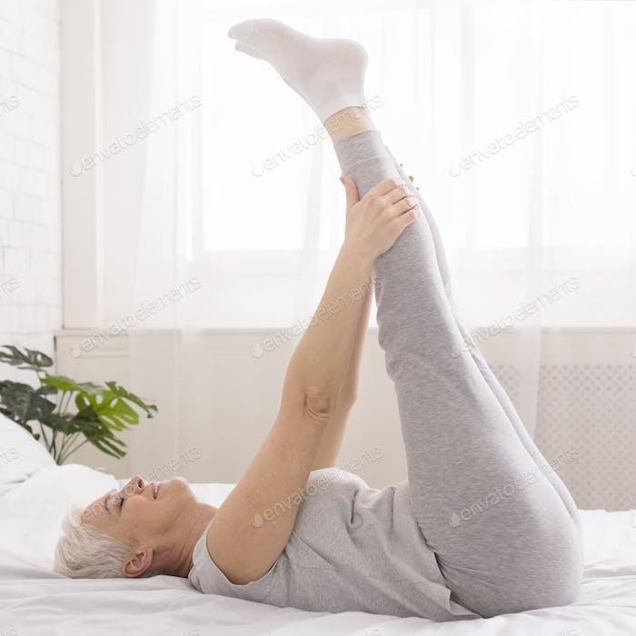 Senior woman doing morning gymnastics, stretching legs on bed