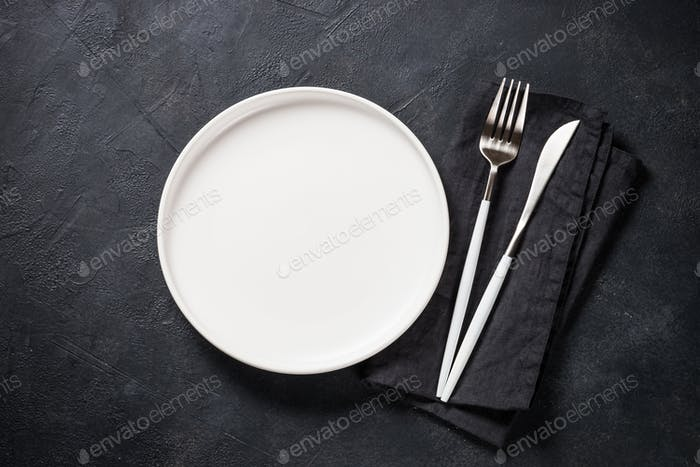 White plate, cutlery and napkin on black table top view