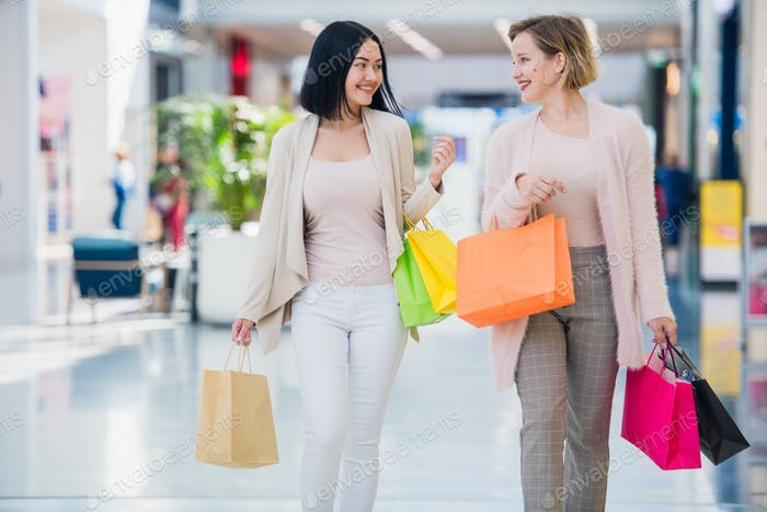 Shopping women talking happy holding shopping bags having fun laughing. Two beautiful young woman