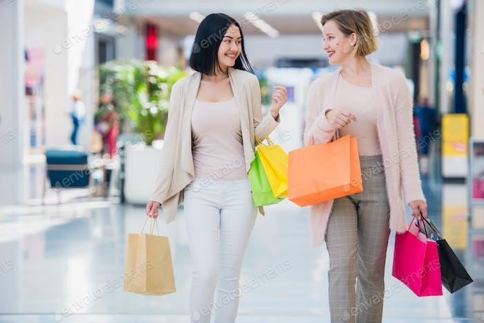 Shopping women talking happy holding shopping bags having fun laughing. Two beautiful young woman