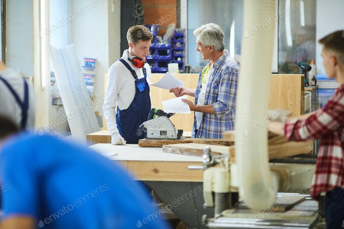 Irritated senior man yelling at inexperienced carpenter for mistakes in sketches