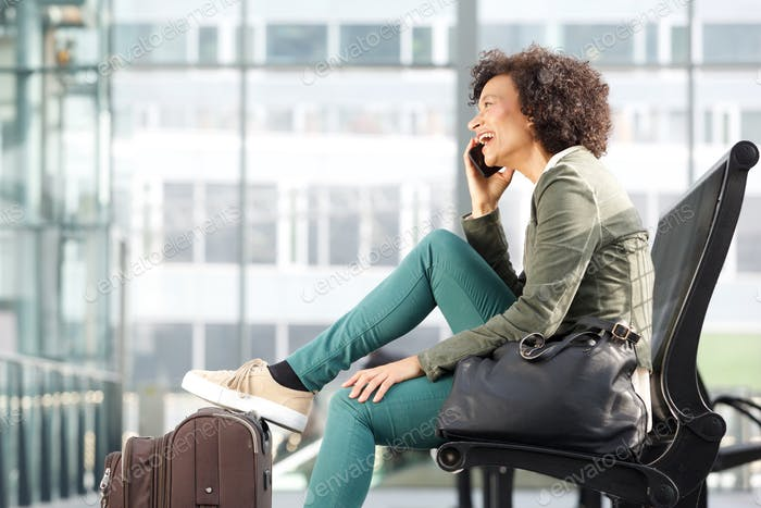 african american woman sitting on bench and talking with cellphone