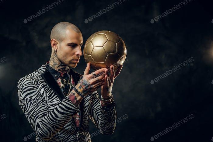 Elegantes tätowiertes männliches Modell posiert mit einem goldenen Fußball in einem Studio