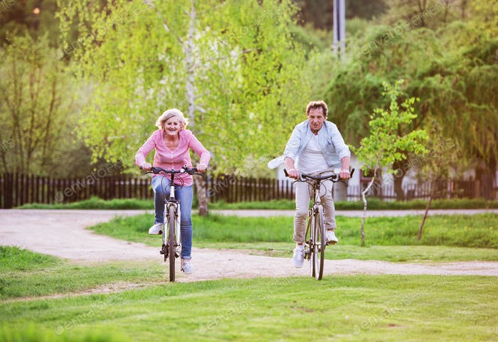 Beautiful senior couple with bicycles outside in spring nature, cycling.