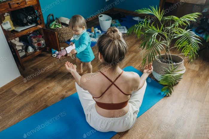 Young mother sitting on the floor, enjoy meditation do yoga exercise at home with his little