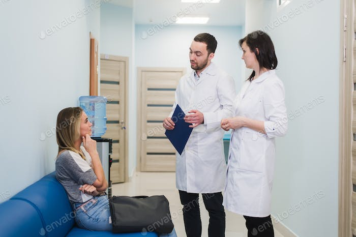 Female Patient Being Reassured By Doctors In Hospital Room