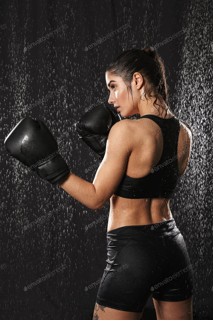 Photo from back of energetic woman boxing wearing gloves and sta