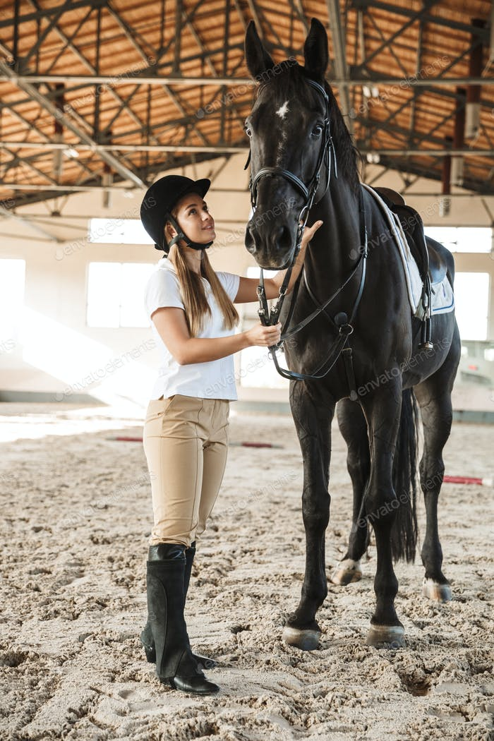 Beautiful woman wearing hat with horse