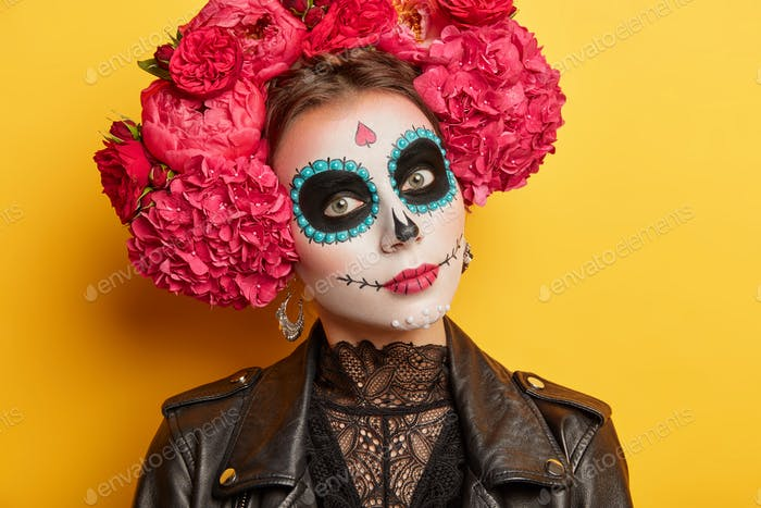 Close up shot of mysterious woman with skull makeup wears flower wreath and black leather jacket pre