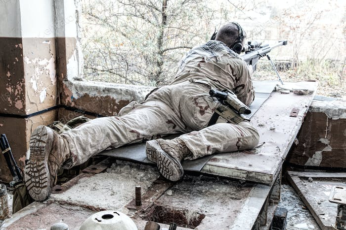 Army sniper in combat readiness on firing position