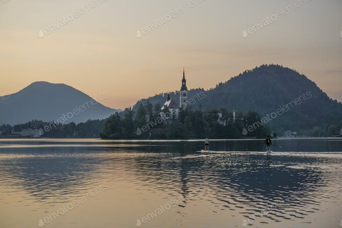People on the sup in the early morning on lake Bled. Just before the sunrise.