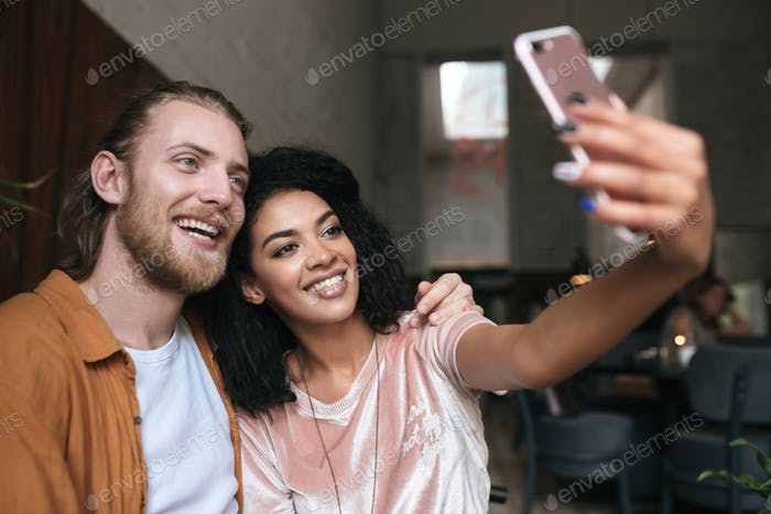Young couple making photos on frontal cellphone camera in restaurant