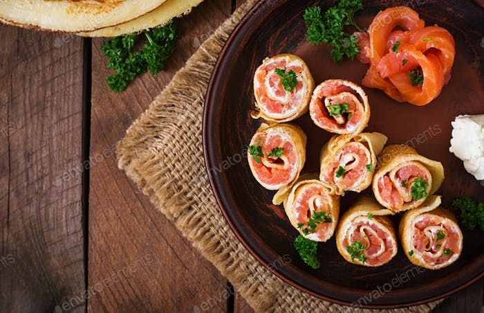 "Appetizing pancakes with salmon and cream cheese ""Philadelphia"". Top view"