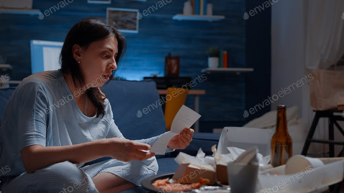 Confused frustrated nevous young woman reading letter, debt notification