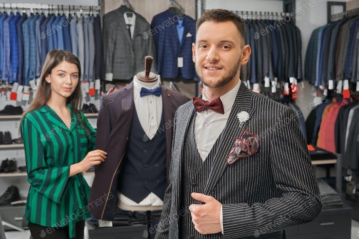 Junger, stilvoller Mann im eleganten Anzug posiert im Geschäft