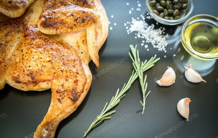 Gegrilltes Huhn mit Zutaten auf dem dunklen Holzhintergrund
