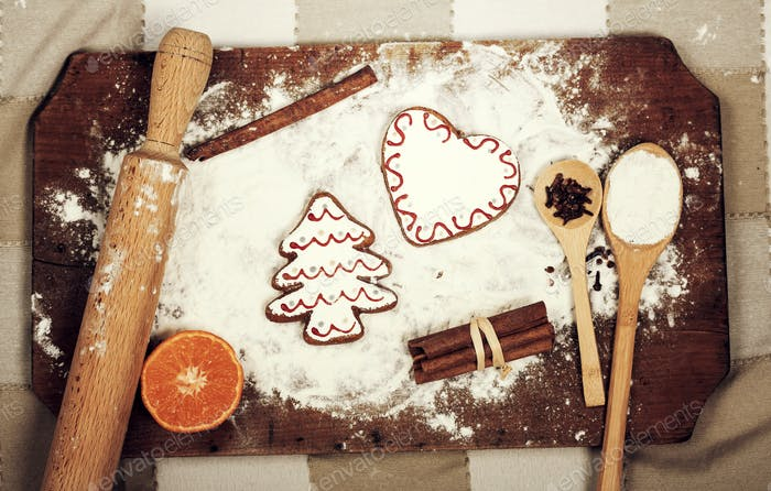 Gingerbread cookies, spices and flour over wooden cutting board
