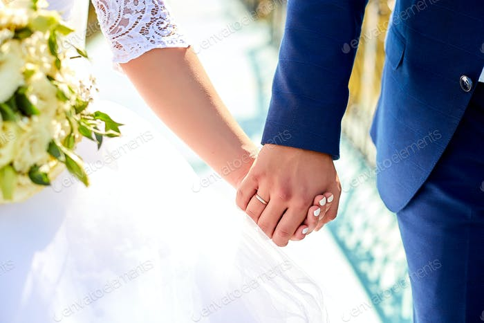 Wedding bouquet holding in a hands of couple.