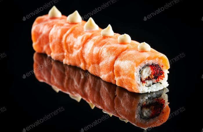 Dragon roll with salmon over black