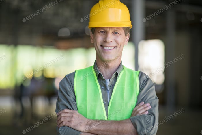 Professional mature architect in protective workwear standing with crossed arms and smiling at