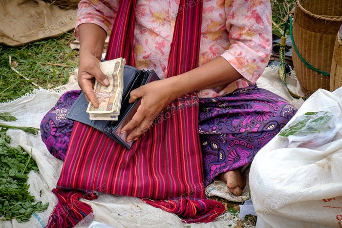Detail of Asian woman in colorful clothes putting money in the purse