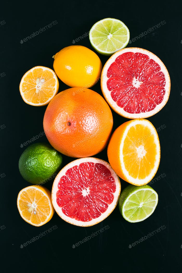 Fresh citrus stihli. Lemons, limes, grapefruit and orange on a black background