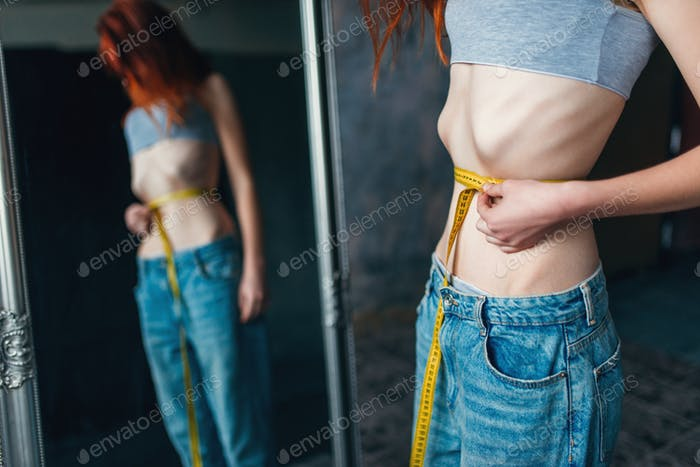 Woman measures waist against mirror, weight loss