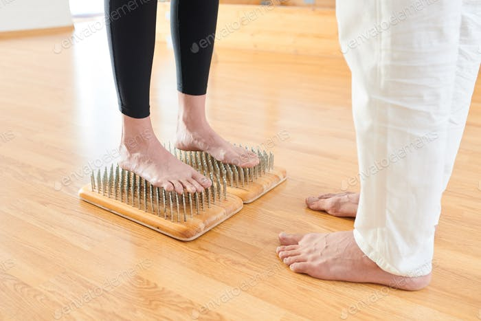 Brave woman standing on bed of nails at yoga practice