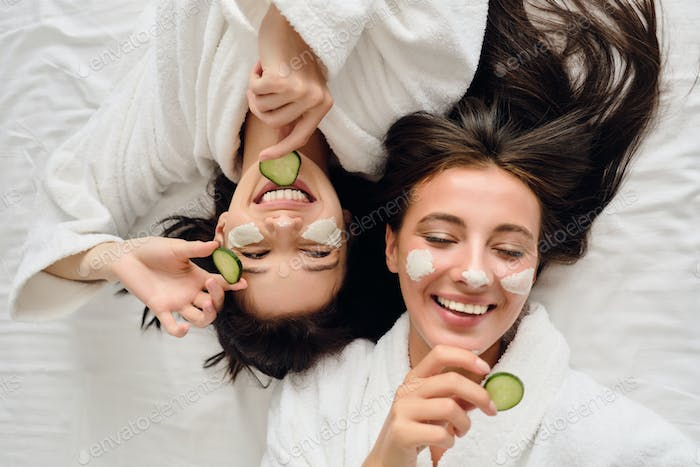 Attractive woman in bathrobes lying in bed with cosmetic mask on faces joyfully