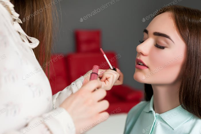 Make up artist applying gloss on woman lips