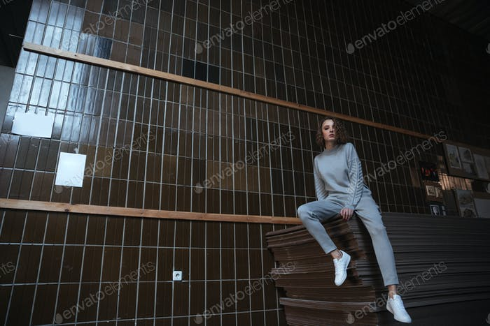 Woman sitting on some wood sheets