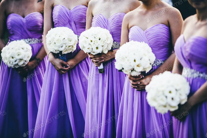 Wedding ceremony with bridesmaids wearing purple dresses and holding white flowers.