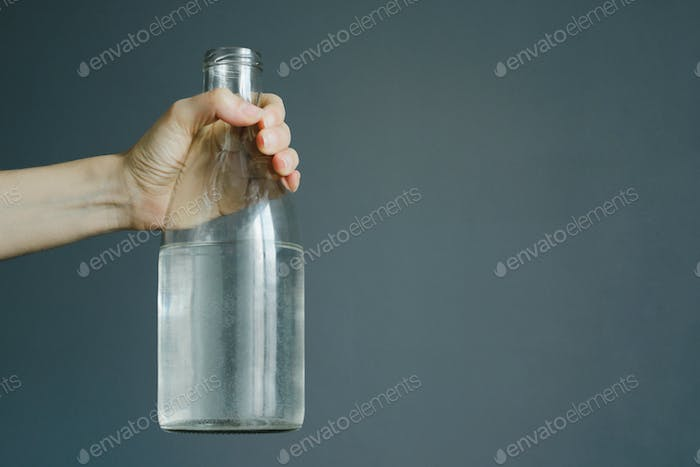 womans hand holds bottle with water on gray wall background