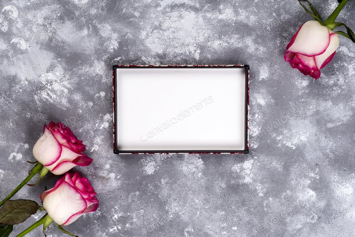 Floral frame: bouquet of pink white roses on stone background with copy space for text.