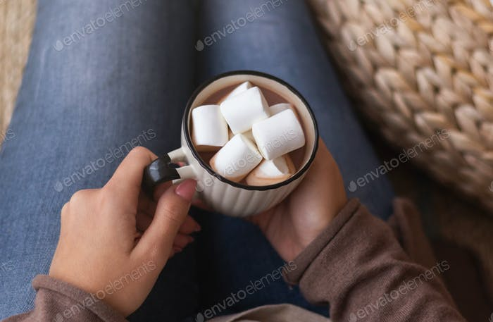 Woman holding cup of aromatic cocoa with marshmallows