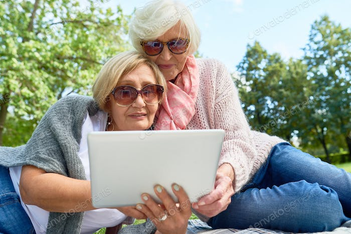 Two Senior Women Using Laptop in Park