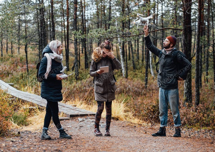 Bearded guy holds quadcopter with raised hand and two girls