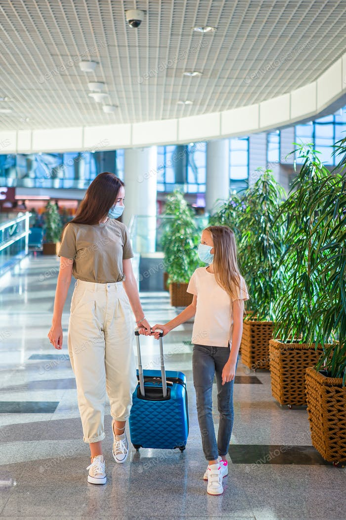 Madre y niña con máscaras nedicales en el aeropuerto. Protección contra Coronavirus y Gripp