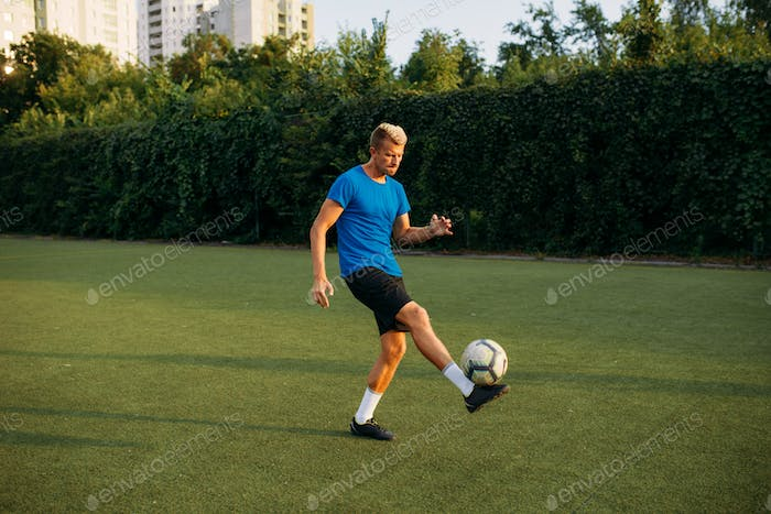 Male soccer player with ball standing on line