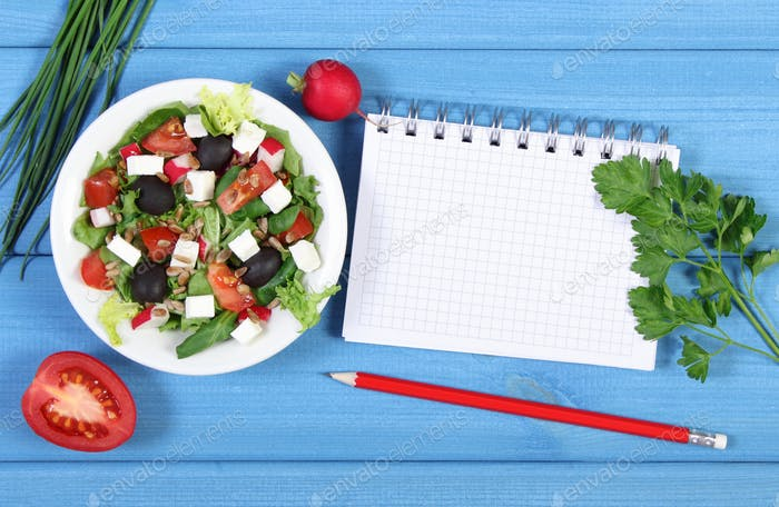 Fresh greek salad with vegetables and notepad for notes, healthy food