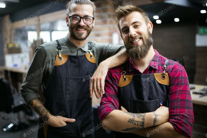 Portrait of young male barbers and hairdressers in barber shop