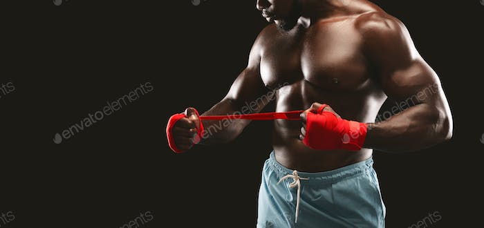Professional african sportsman rolling boxing wraps over wrists before competitions