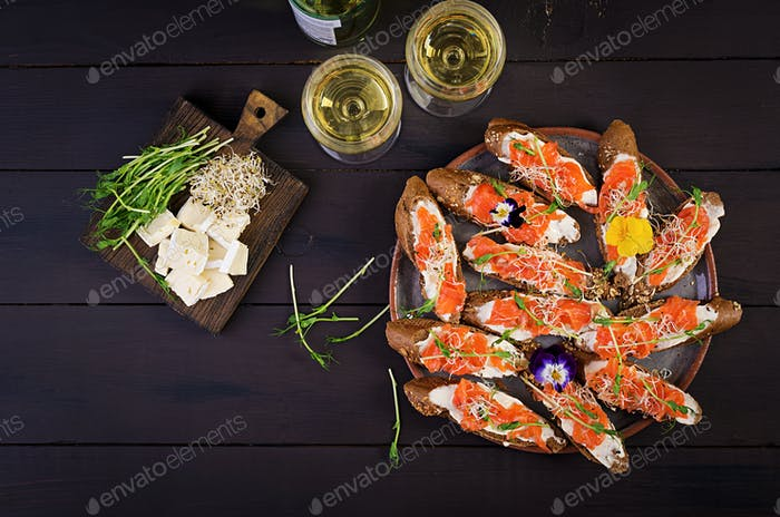 Salmon sandwiches with cream cheese and microgreen on wooden table. Canape with salmon. Top view