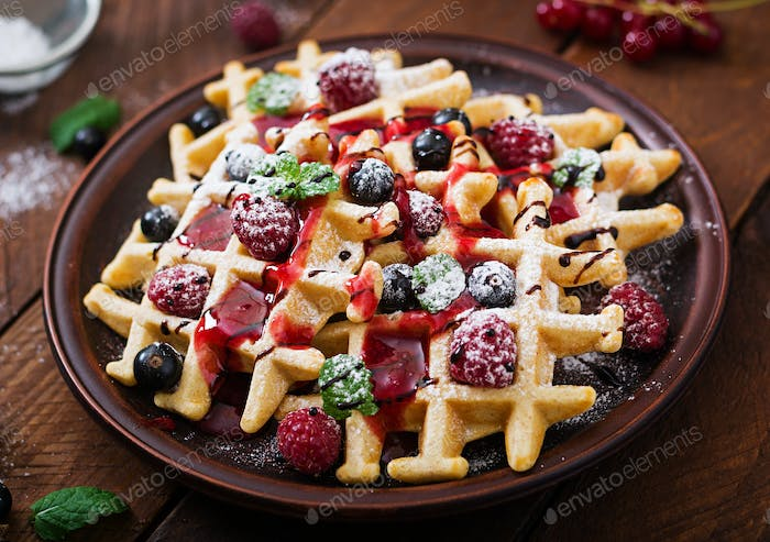 Belgium waffles with raspberries, chocolate and syrup on a plate.