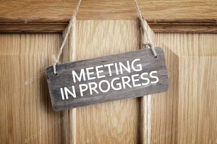Meeting in progress sign on office door